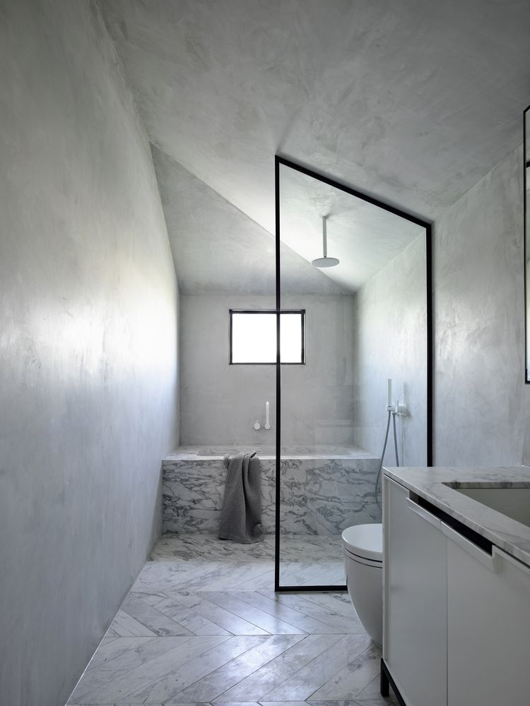 There's a large marble clad bathtub and cocnrete walls plus a window that brings light in