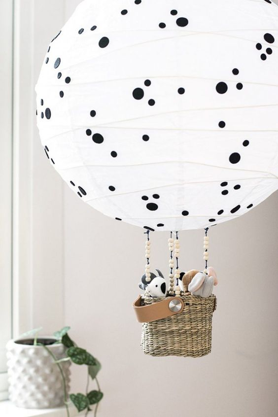 a Regolit lampshade turned into a hot air balloon lamp with polka dots and toys in the basket