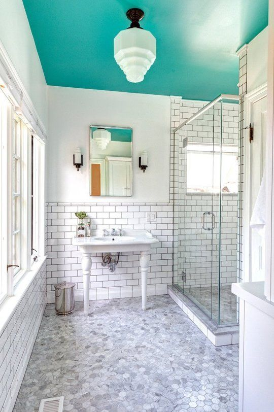 a neutral bathroom spruced up with a bold aqua-colored ceiling that brings color and makes the space non-boring