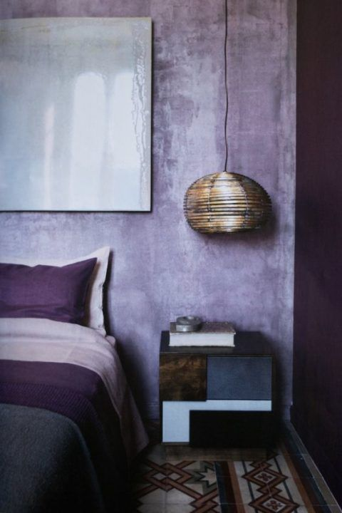 lilac plaster walls and touches of deep purple make up a bold and ultra modern bedroom