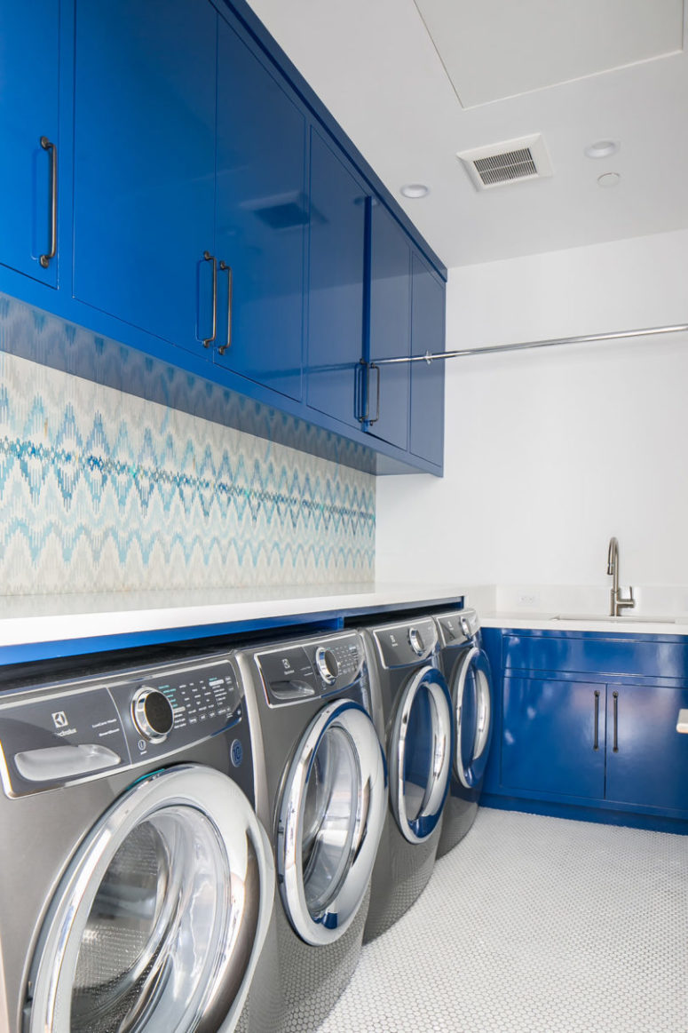 The laundry room continues the blue and white color scheme, which can be seen throughout the house