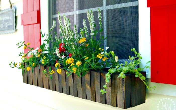 a dark stained picket fence flower box with colorful blooms is a bold idea and red shutters add to the look