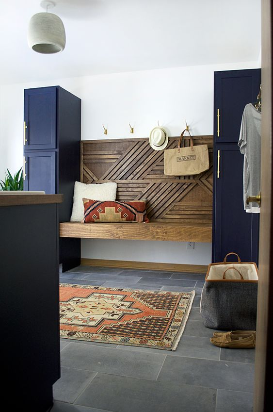 a floating geometric built-in bench between two navy cabinets that are secondary ones