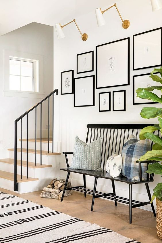 a vintage black bench sets the tone of this entryway and printed pillows add to it