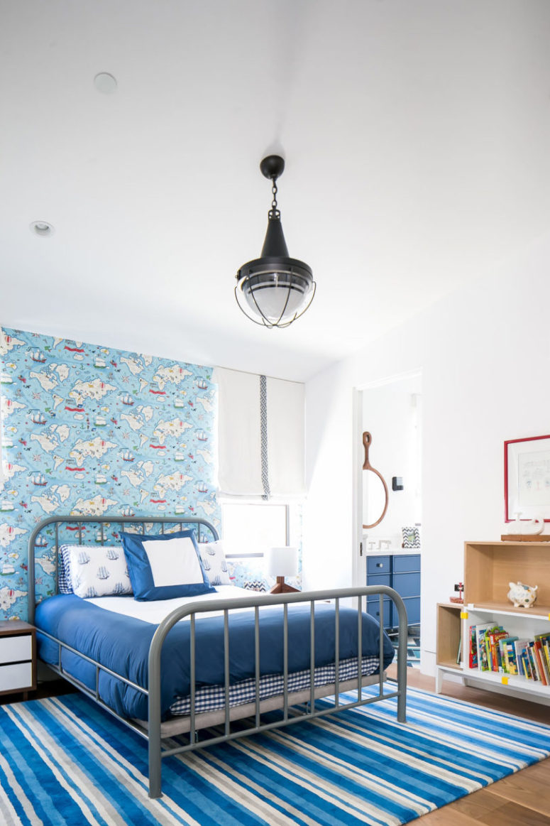 The kid's bedroom is done with a nautical feel, with catchy wallpaper and rugs