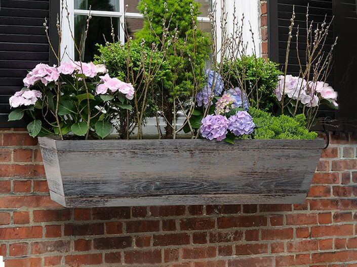 a distressed wood window box with pastel blooms and foliage adds a cozy feel and traditional touch