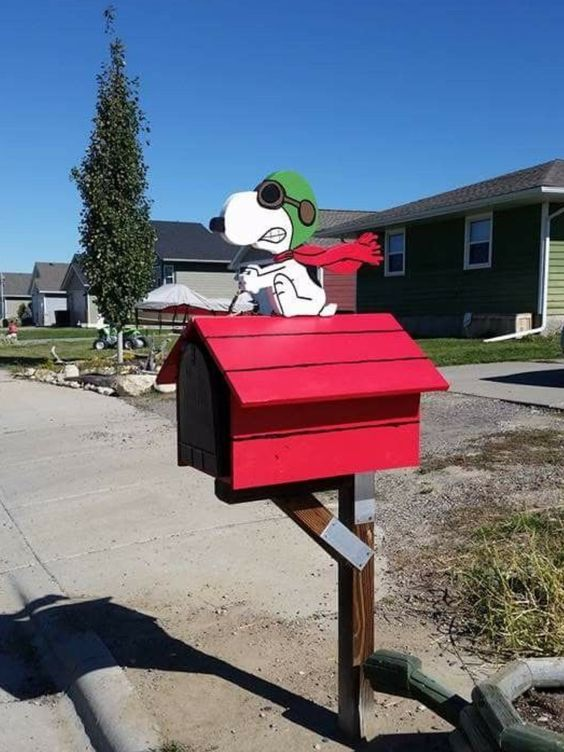 a hot red mailbox with a fun toon doggie is a whimsy and quriky idea that will catch an eye every time