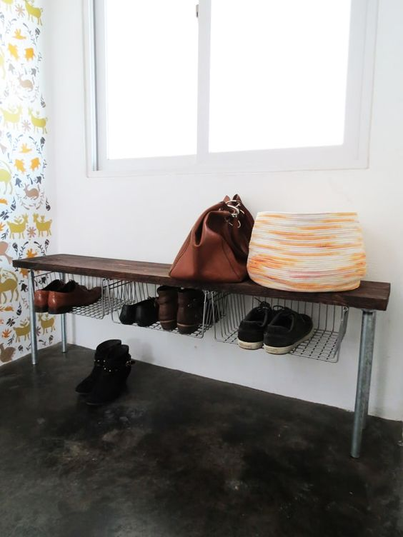 a rough entryway bench with metal leg, a wooden seat and wire baskets attached under the seat