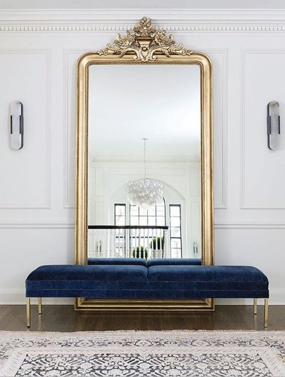 a beautiful navy velvet bench with gold legs is a refined and chic statement for the entryway