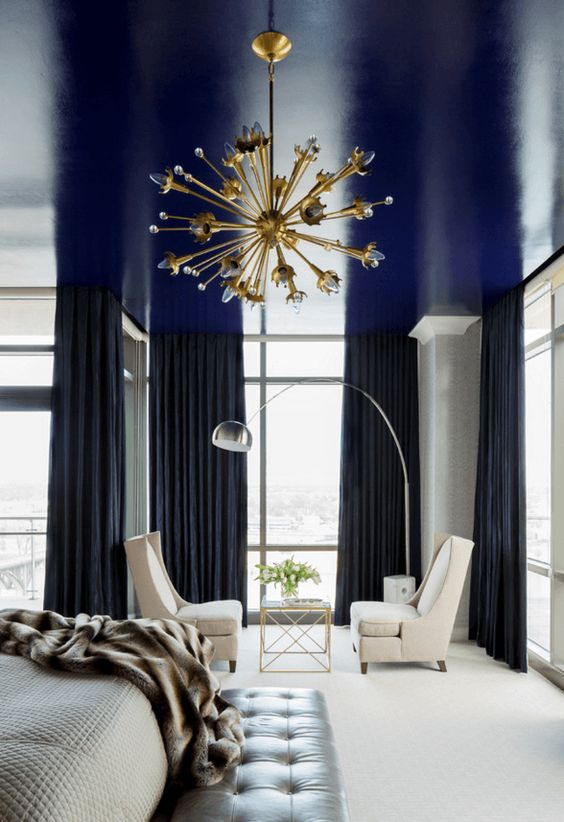 a shiny navy ceiling is a cool way to add a touch of color and a moody feel to the monochromatic bedroom