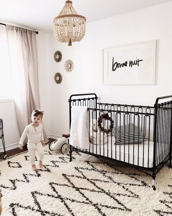 a vintage-inspired black iron crib is a refined and chic piece that brings a sophisitcated touch