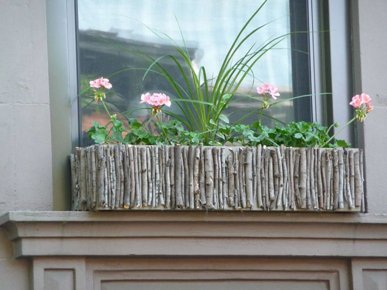 a wig and branch window box with greenery and pink blooms is a great idea to add a natural feel to your window