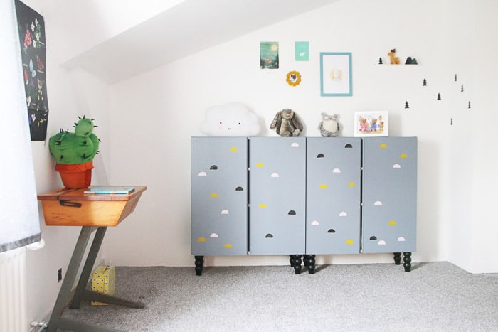 an IKEA Ivar cabinet customized with grey paint, cloud prints and black legs for a nursery or a kids' room