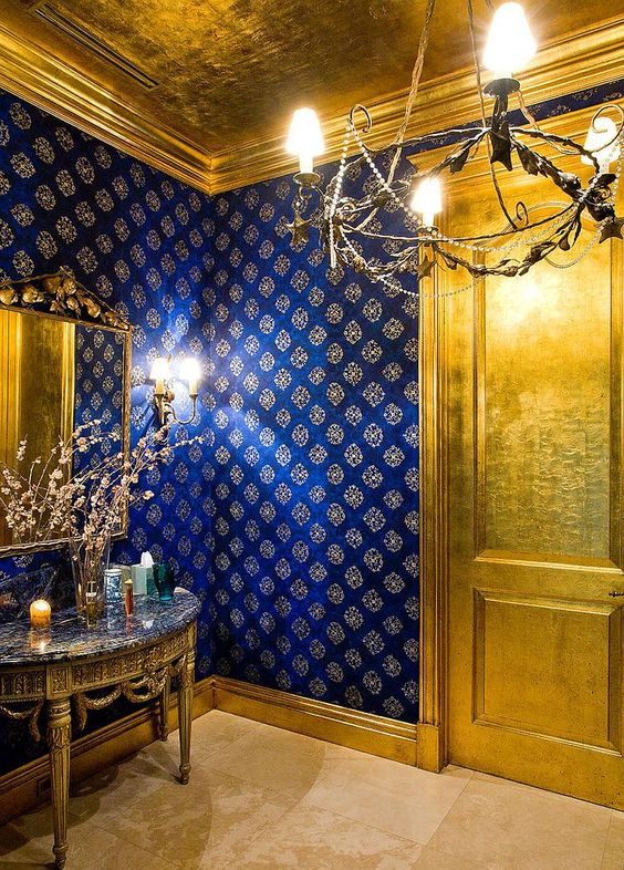 an exquisite and super chic powder room done with a gold door, a gold vanity and a ceiling that matches