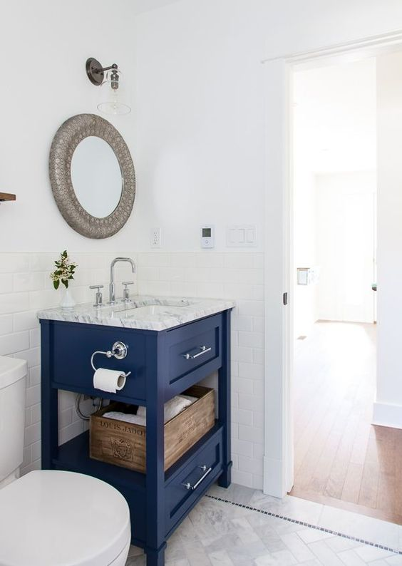 a bright blue small vanity with a stone countertop and some storage space is a bright statement