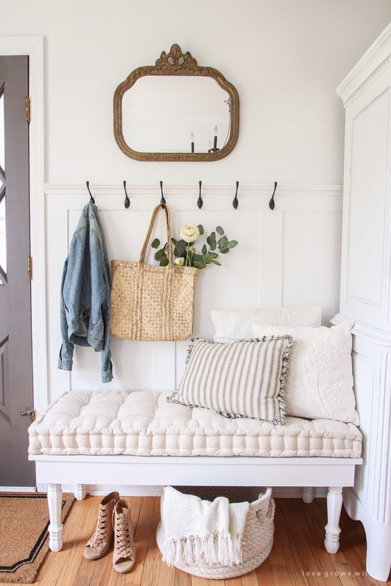 a cozy vintage bench with a super soft cushion gives a tone to this entryway