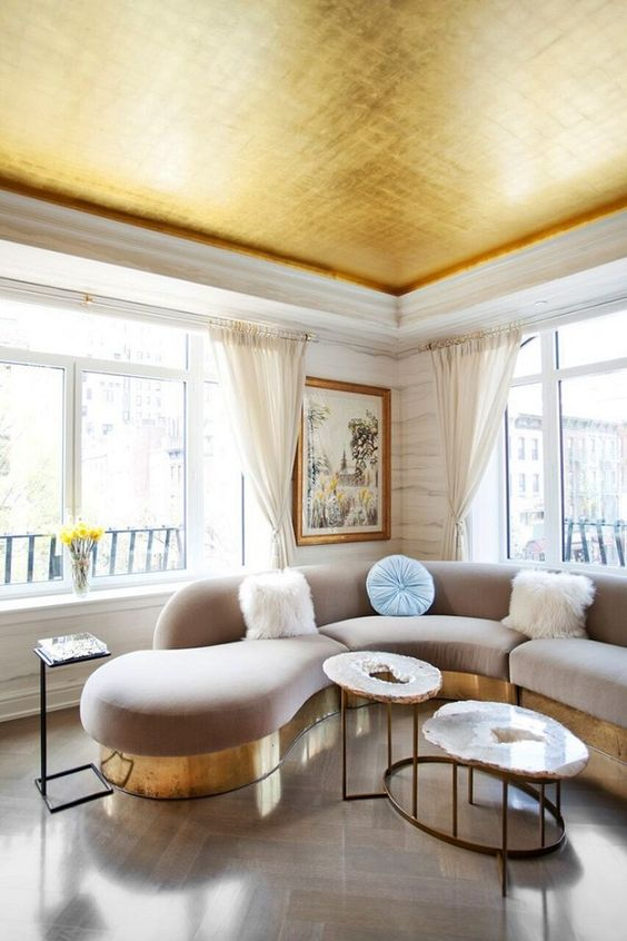 a shiny gold ceiling echoes with the furniture bases and makes the space more glam