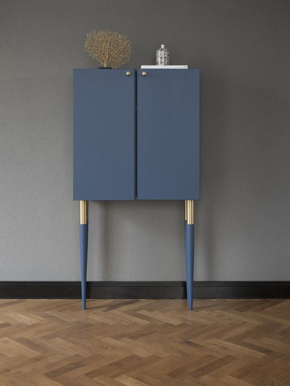 a very chic and refined hack of an Ivar cabinet in navy, with tall gold and navy legs and gold knobs