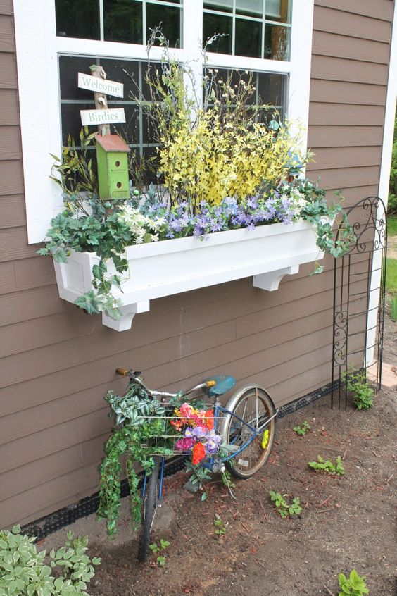 a white window box planter with pastel spring blooms and a little bird house for more coziness and sweetness