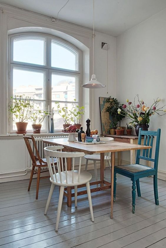 an eclectic dining space with various chairs and a dining table and lots of different finishes