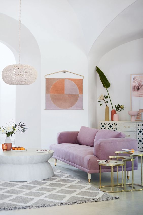 a contemporary living room done in neutrals and with a lilac sofa as a bright touch and centerpiece