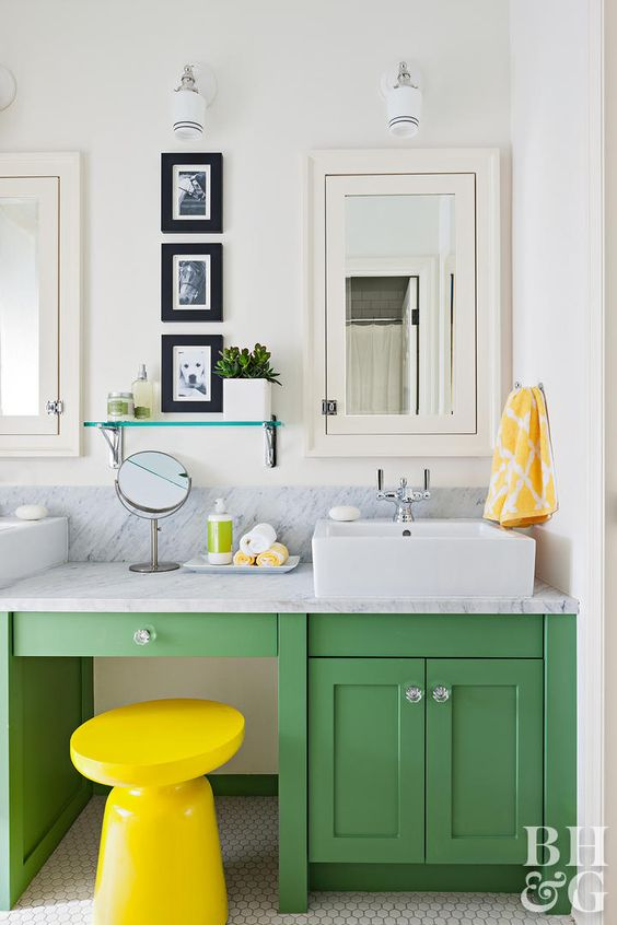 a green vanity and a bold yellow stool is an ultimate combo for a contemporary bathroom