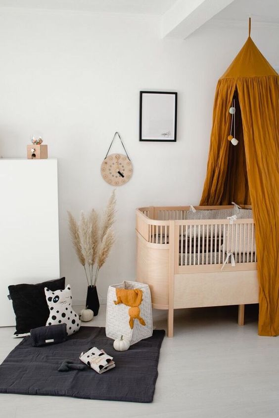 a simple and modern plywood crib with a rust colored canopy for a bold and cool nursery