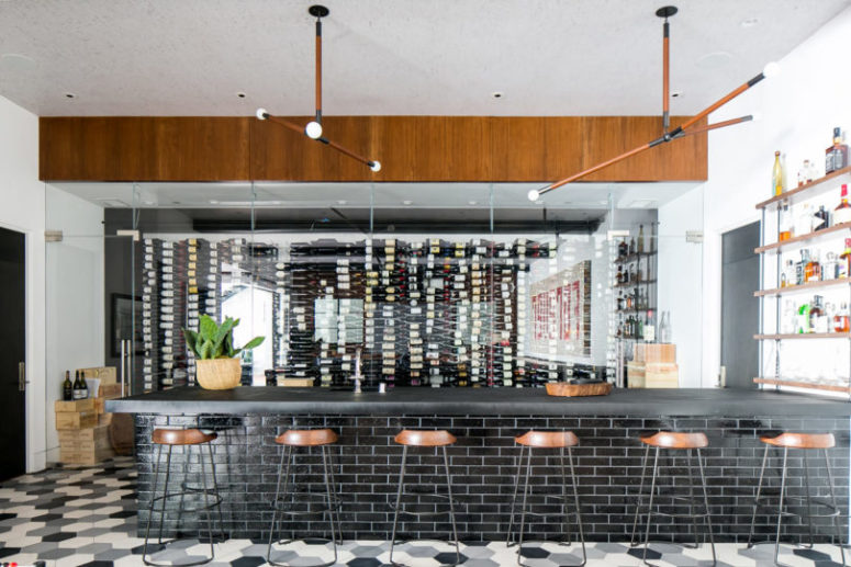 There's a wine cellar clad with glass and a large bar space
