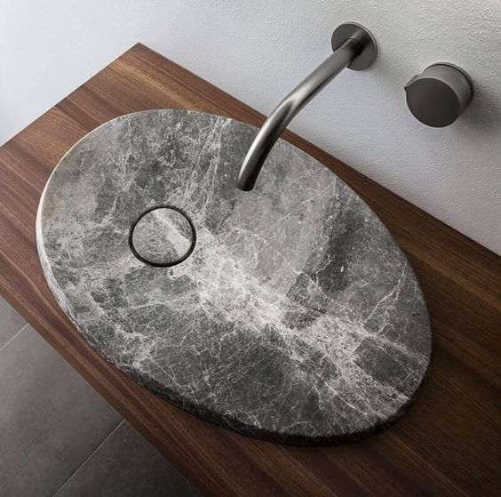 a fantastic oval stone modern sink to make a statement in a bathroom