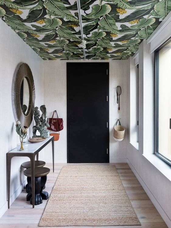 an entryway with a bright ceiling covered with tropical leaf print wallpaper that adds color and print to the space