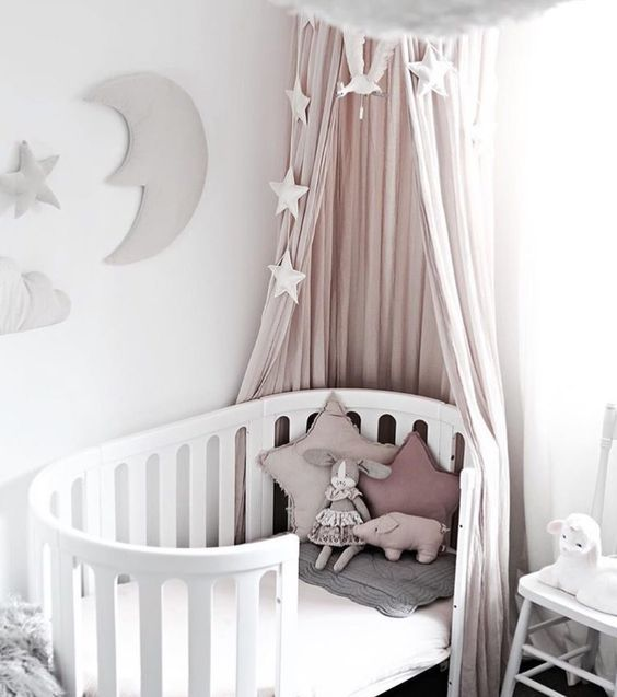 a curved crib with a blush canopy, pillows and stars for a beautiful girl's nursery