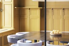 17 a dining space with yellow walls and lilac and brass chairs with a laconic and modern design