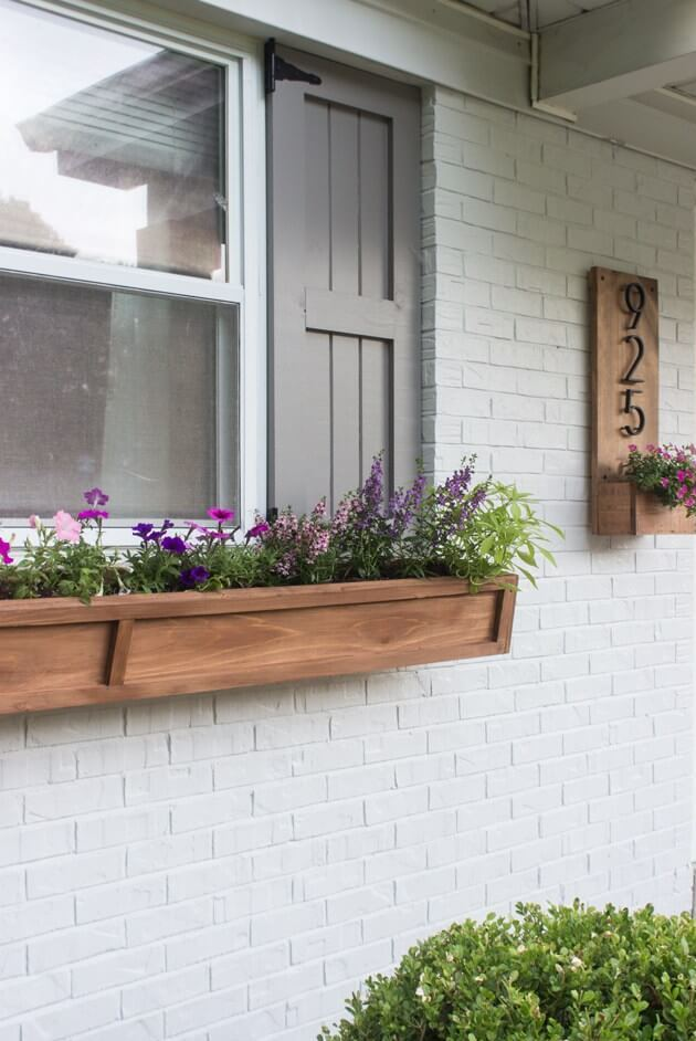 a simple and modern wooden flower box with bold purple and pink blooms adds a contemporary feel
