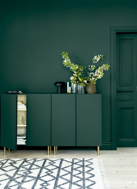 dark green Ivar cabinets with gold legs in front of a matching wall create a gorgeous moody space