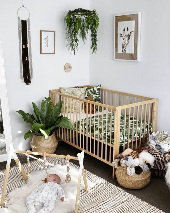 a boho nursery with potted greenery, macrame, wicker baskets and a printed rug