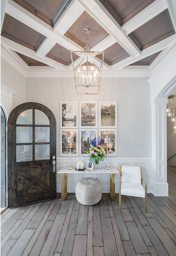 a chocolate brown and white coffered ceiling adds a refined and chic touch to the entryway and brigns timeless elegance