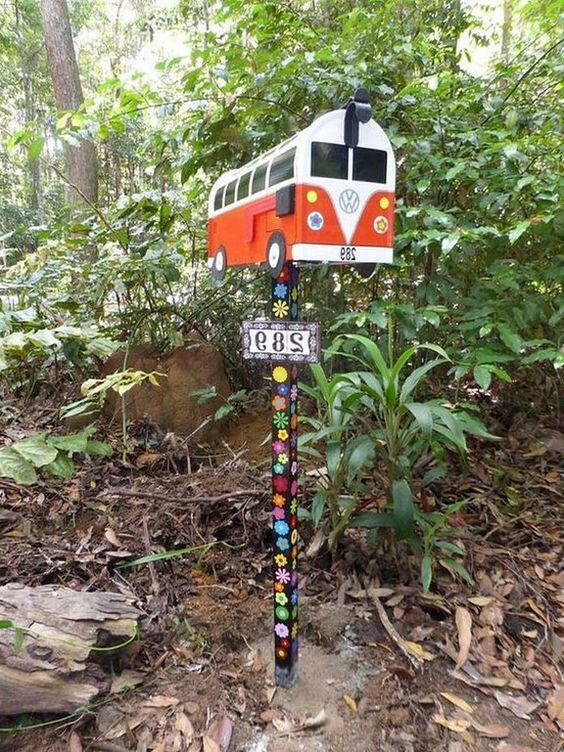 a fun mid-century modern van mailbox on a wooden stand decorated with painted flowers is a cool boho chic idea