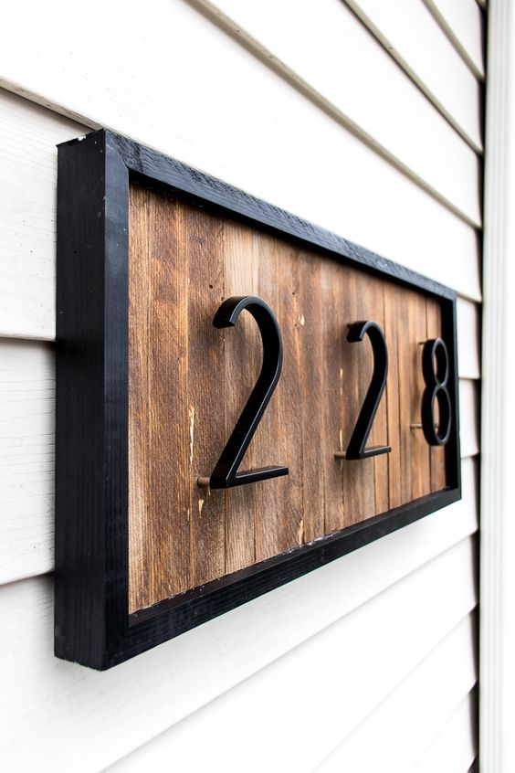 a modern house number sign with wood shims and black metal numbers and frame looks stylish and very laconic