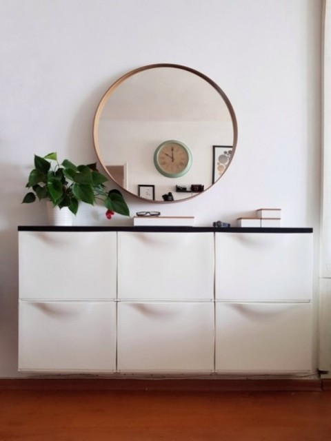 a stylish entryway floating console with a black tabletop is a chic contemporary idea, which fits even a small space