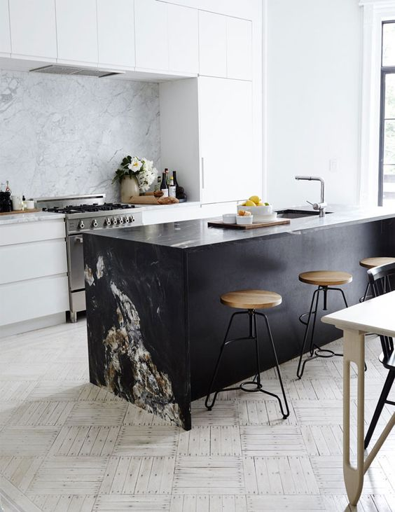 a black kitchen island with a stone waterfall countertop contrasts the space and makes a statement