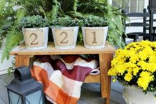 19 a front porch with a table and planters on them, plant something and add burlap house numbers on it for a rustic feel