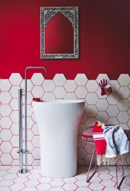 a hot red statement wall and hot red grout that accents the hex tiles on the wall and floors