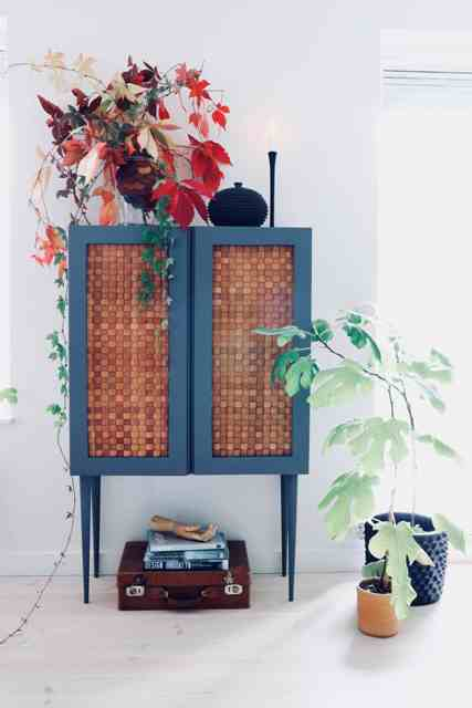 an IKEA Ivar cabinet painted blue, placed on tall legs and clad with corks is a bold and very whimsical idea