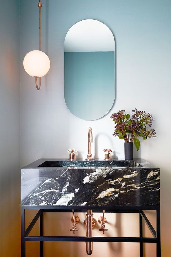 an edgy black marble vanity resting on a blackened steel vanity and accessorized with copper touches