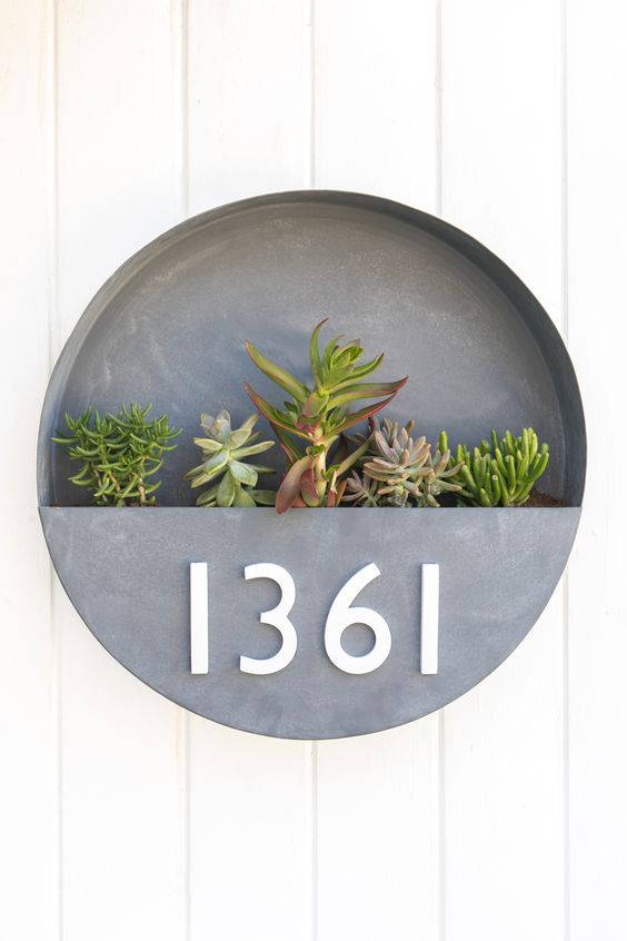 a brushed metal round wlal planter with numbers and succulents in it is a chic idea with a mid-century modern feel
