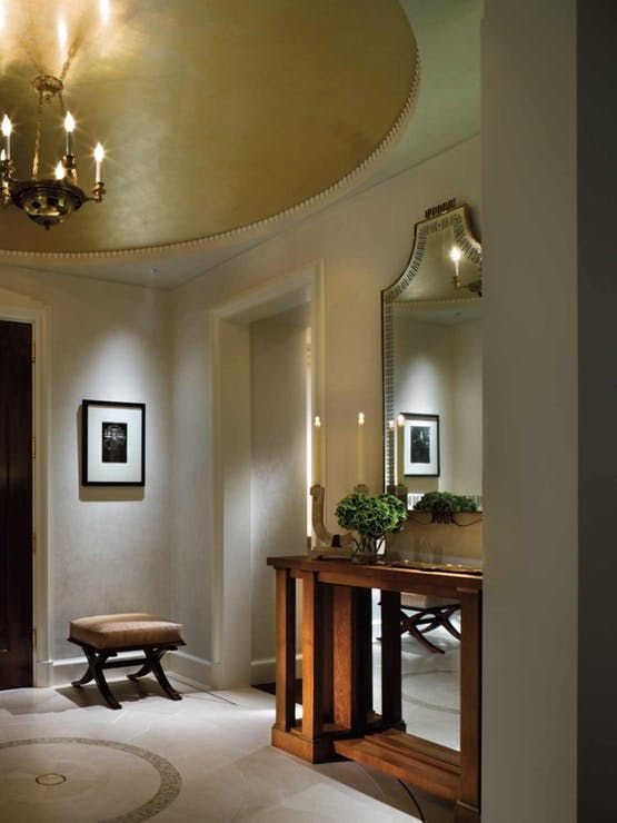 a contemporary and refined entryway spruced up with a round gold ceiling medallion and a chic chandelier