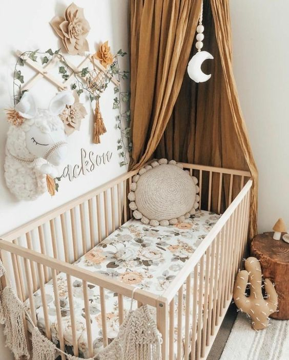 a cozy boho space with greenery, a toy animal head, flowers and tassels for a little girl