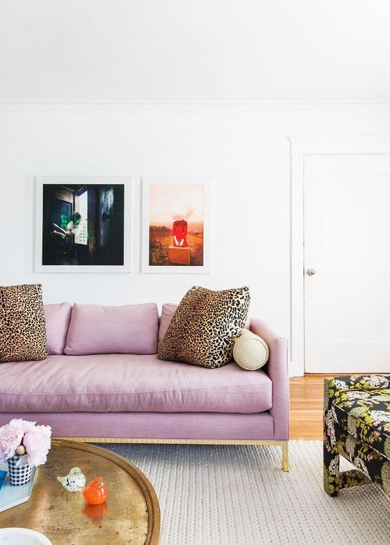 a lilac and gold sofa and leopard print pillows as accessories create a bold look and a color statement