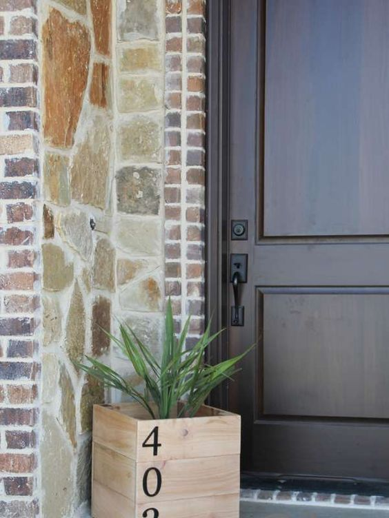 a wooden planter with some greenery and table numbers on them is a simple and fast DIY project for any porch