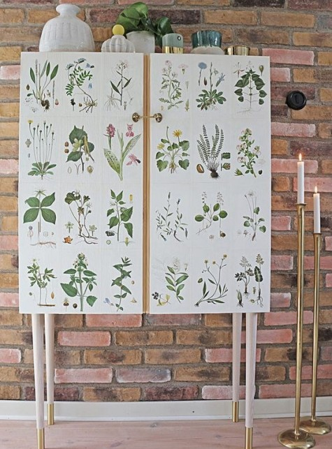 an IKEA Ivar cabinet placed on tall legs and decorated with vintage plant pictures is a whimsy hack to try